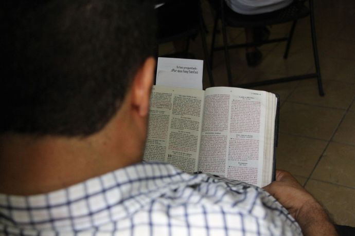 El Salvador: A member of the Local Church reading the Bible during a Missionary service. More Info