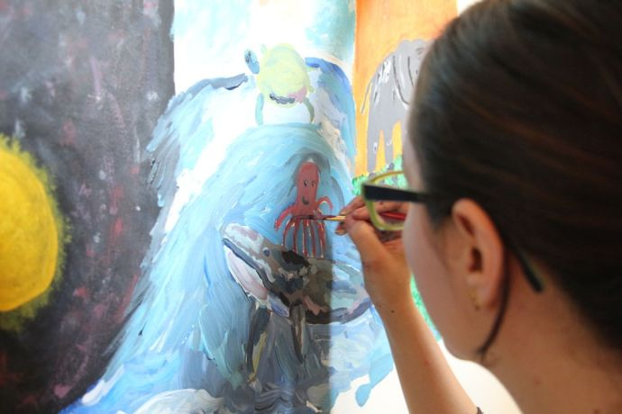 El Salvador: An volunteer paiting a mural about Gods creation at Love Link. More Info