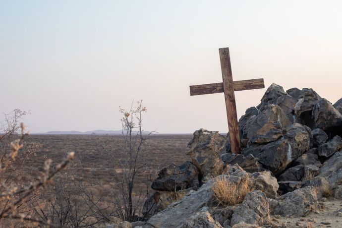 Namibia: A cross among rocks in Namibia. Photo by Rebecca Rempel. More Info