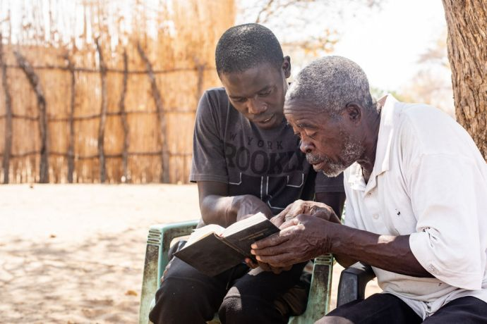 Namibia: Two men look at a Bible passage in a village in Namibia. Photo by Rebecca Rempel. More Info