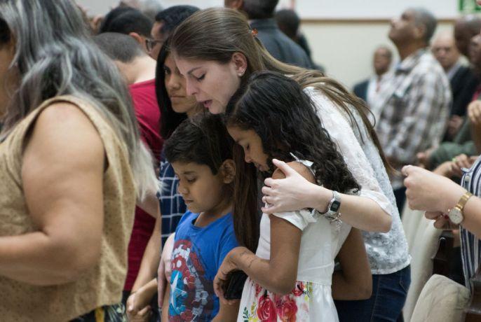 Brazil: Rio de Janeiro, Brazil :: A mother prays with her children at a prayer event on shore. More Info