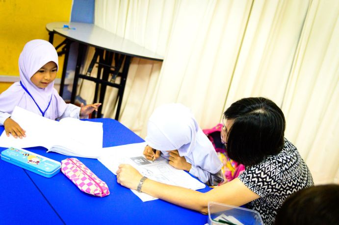 South East Asia: Teacher teaching lessons and helping the students. More Info