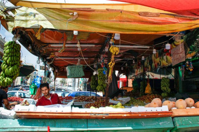 Near East: People shopping at a local shop that sells fruit and vegetables. Photo by Johanna Bird. More Info