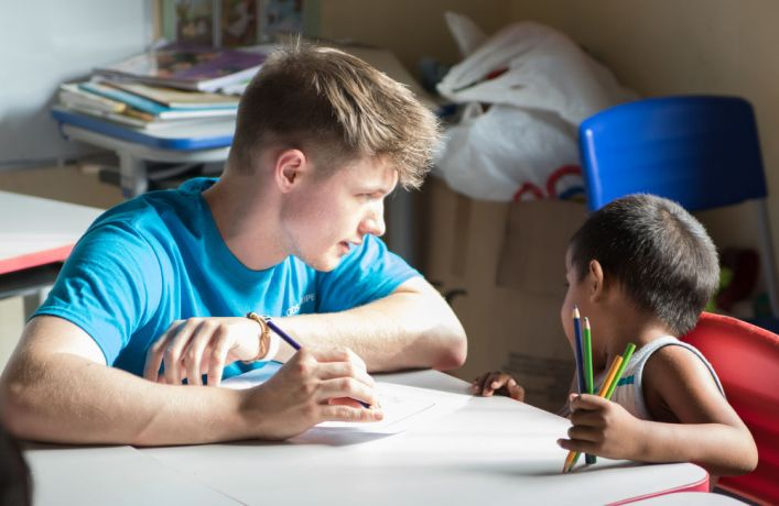 Brazil: Belém, Brazil :: Peter Carrigan (United Kingdom) helps a child from a Venezuelan refugee community to finish his drawing. More Info