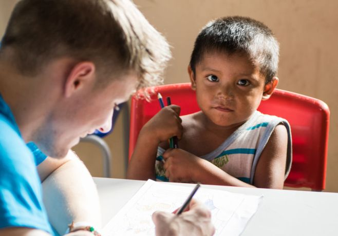 Brazil: Belém, Brazil :: Peter Carrigan (United Kingdom) helps children from a Venezuelan refugee community with their drawings. More Info