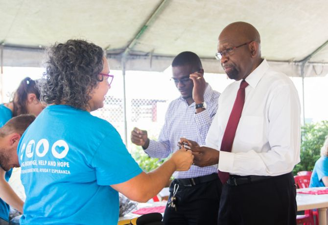 Guyana: Georgetown, Guyana :: Roxy Flores (Mexico) gives a pair of glasses to a pastor. More Info