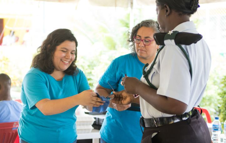 Guyana: Georgetown, Guyana :: Valeria Balderas (Mexico) gives a pair of glasses to a prison guard. More Info