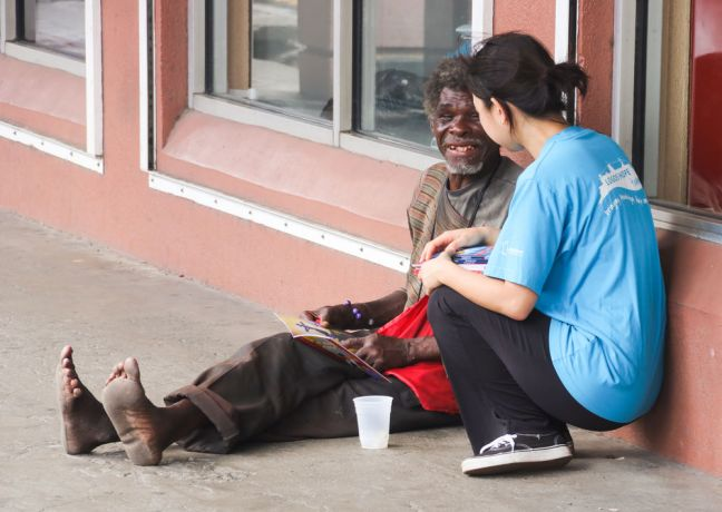 Saint Vincent & the Grenadines: Kingstown, Saint Vincent and the Grenadines :: Hannah Kim (South Korea) gives a Gospel of John to a homeless man. More Info