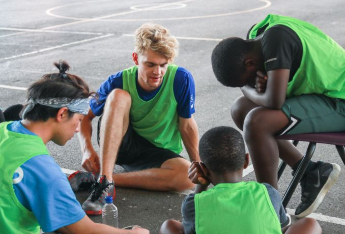 Barbados: Bridgetown, Barbados :: Liam Packwood (Scotland) prays with teenagers at a church basketball tournament. More Info