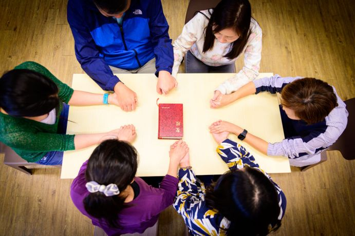 Hong Kong: Staff workers pray around a table. More Info