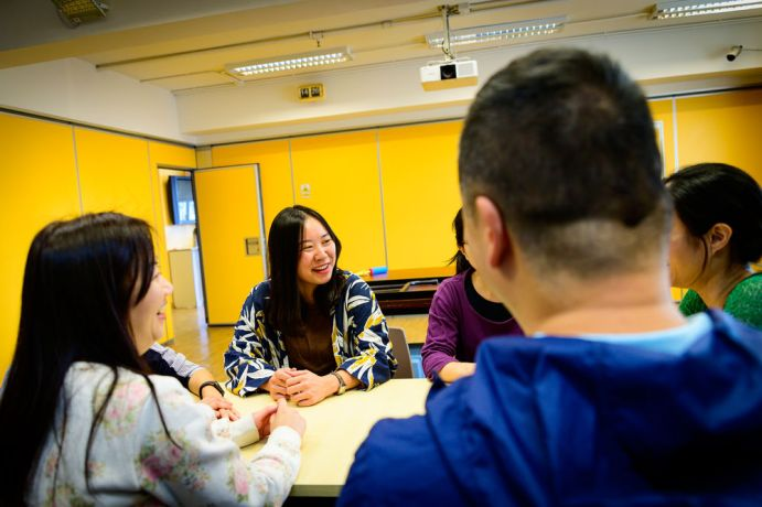 Hong Kong: Staff workers enjoying fellowship around a table. More Info