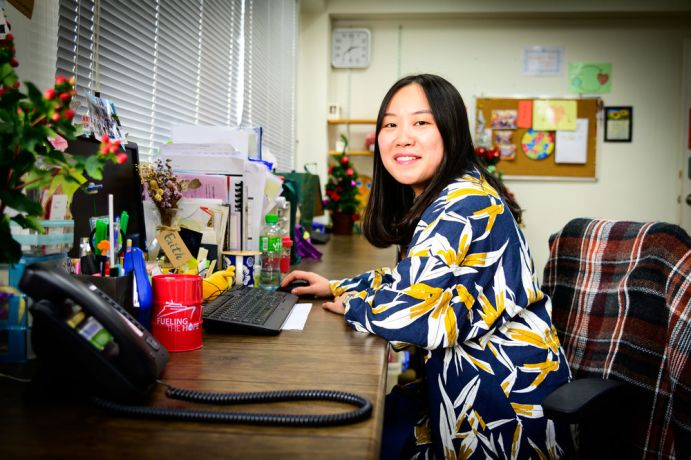 Hong Kong: Staff worker at her desk. More Info
