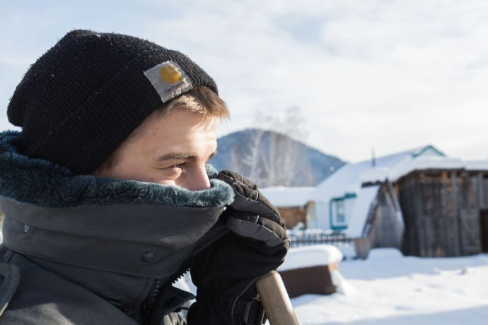 Russia: Man shields his face from the cold in a Russian village in winter. More Info