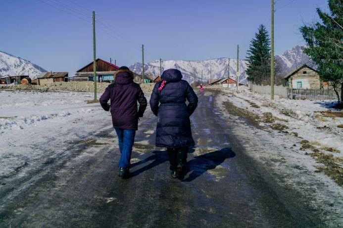 Russia: People walking towards a Russian village in winter. More Info