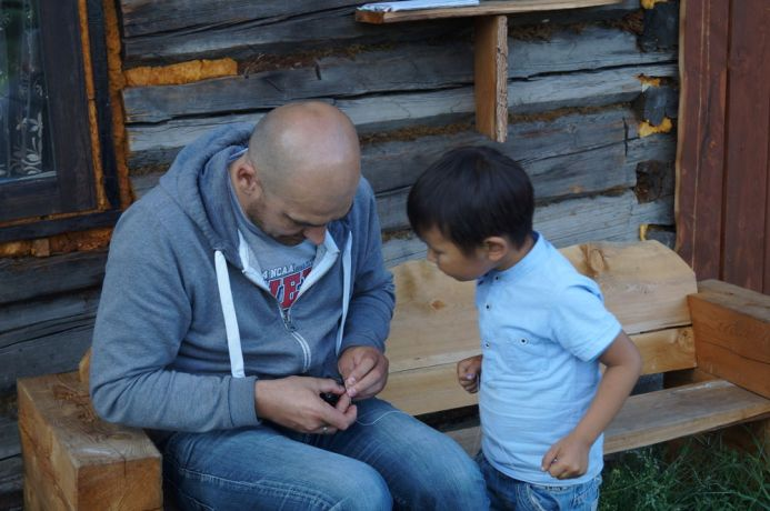 Russia: A man from an unreached ethnic group explains to a young boy how to use a toy. More Info