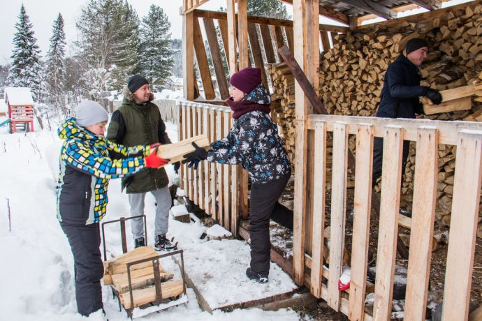 Russia: Young people handing out firewood at a home in winter. More Info