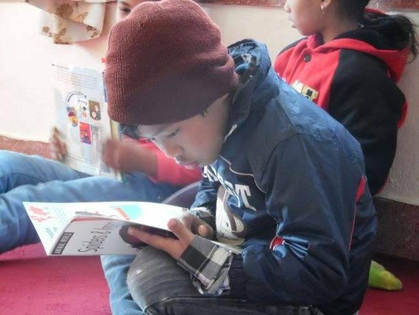 Russia: Russian woman shares the Gospel in South-East Asia. Child reading book. More Info