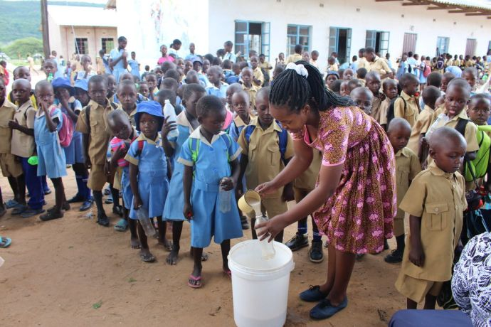 Zimbabwe: An OM worker feeds children at the Siabuwa Primary School in Zimbabwe. More Info