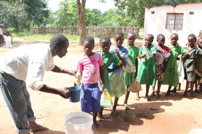 Zimbabwe: A member of the Mulambe parents committee serves the Mahewu drink to school children. In drought-hit Zimbabwe, schools are no longer just places to learn algebra and mathematics but are on the frontline to help feed children. More Info
