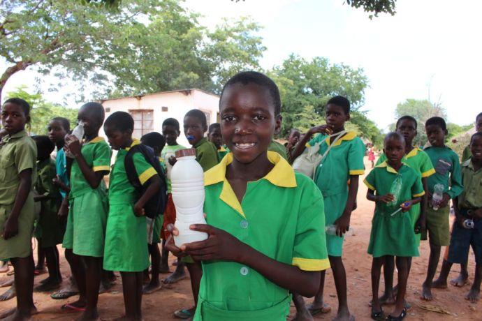Zimbabwe: A schoolgirl displays her bottle of Mahewu. More Info