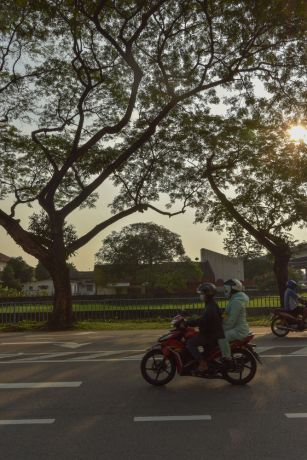 Malaysia: A couple wearing face masks rides down a street in Kuala Lumpur, Malaysia showing the countrys lockdown measures in action to prevent the spread of COVID-19. More Info