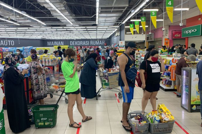 Malaysia: Shoppers wearing face masks stand in line at a grocery store in Kuala Lumpur, Malaysia showing the countrys lock down measures in action to prevent the spread of COVID-19. More Info