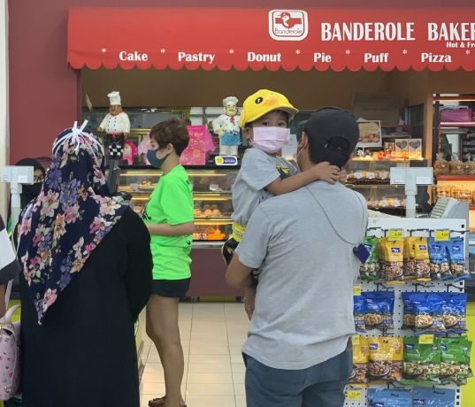 Malaysia: A young girl and her father wearing face masks stand in line at a grocery store in Kuala Lumpur, Malaysia showing the countrys lock down measures in action to prevent the spread of COVID-19. More Info