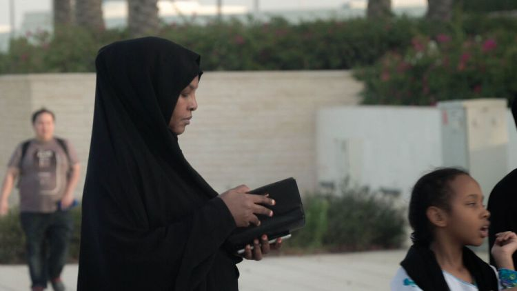 Arabian Peninsula: A Muslim woman checks her purse while waiting to enter a mosque. Photo by Jay S. More Info