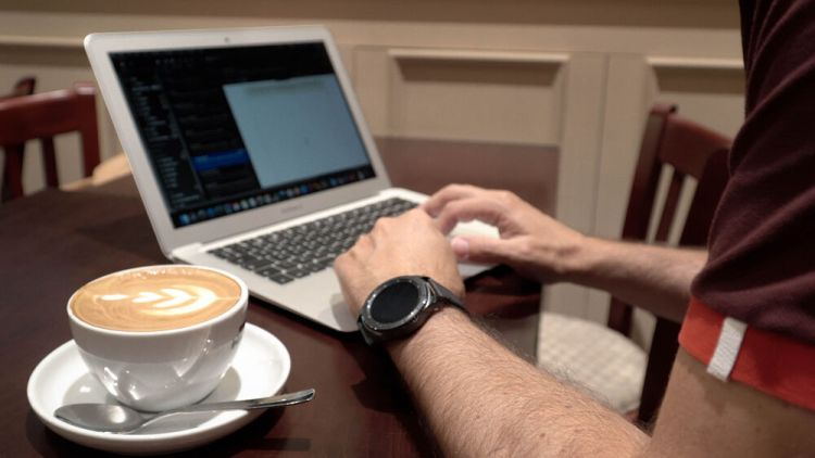 Arabian Peninsula: A marketplace worker spends an afternoon working remotely in a local coffee shop. Photo by Jay S. More Info
