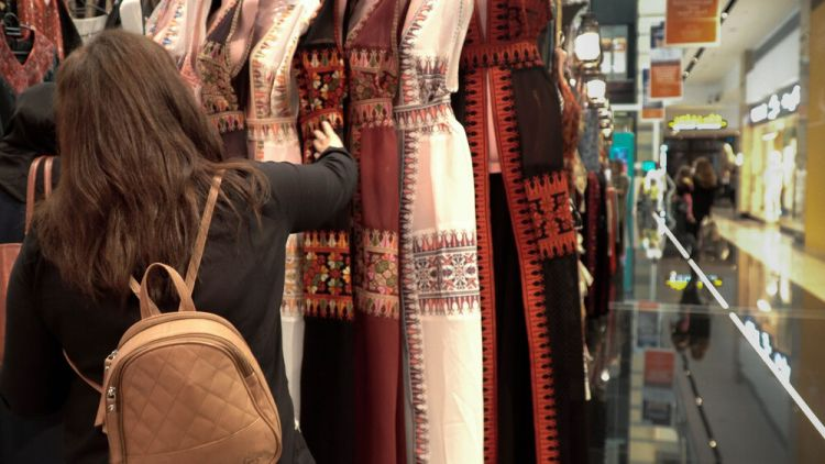 Arabian Peninsula: A worker browses a display of traditional Arabian dresses at a mall in the Middle East. Photo by Jay S. More Info