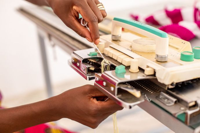 Africa: A woman working on a knitting machine in north-central Africa. Photo by Rebecca  R. More Info