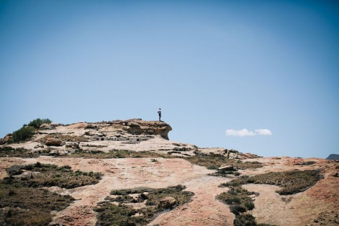 Lesotho: A solitary man standing on a mountaintop in Lesotho. Lesotho is a small mountainous country completely surrounded by South Africa. Photo by Doseong Park. More Info