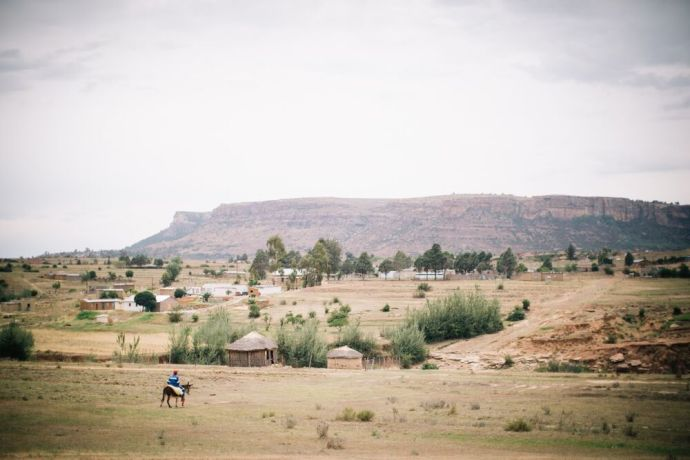 Lesotho: Man on a donkey arrives at his village in Lesotho. Lesotho is a small mountainous country completely surrounded by South Africa. Photo by Doseong Park. More Info