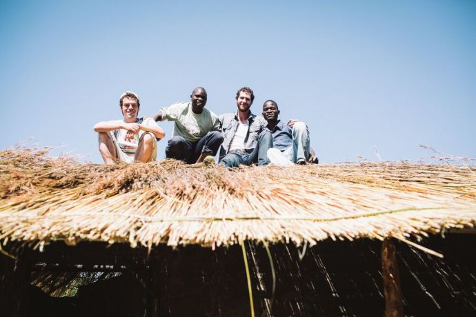 Malawi: Men sit on a newly completed thatched roof. Photo by Doseong Park. More Info