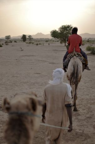 Africa: People ride camels through the desert in Africa. Photo by Andrew Fendrich. More Info