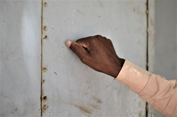 Africa: A hand knocks on a door in Africa. Photo by Andrew Fendrich More Info