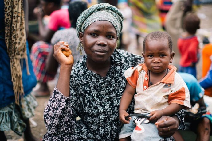 Ghana: A woman holding her child smiles for a portrait in Ghana. Photo by Do Seong Park. More Info