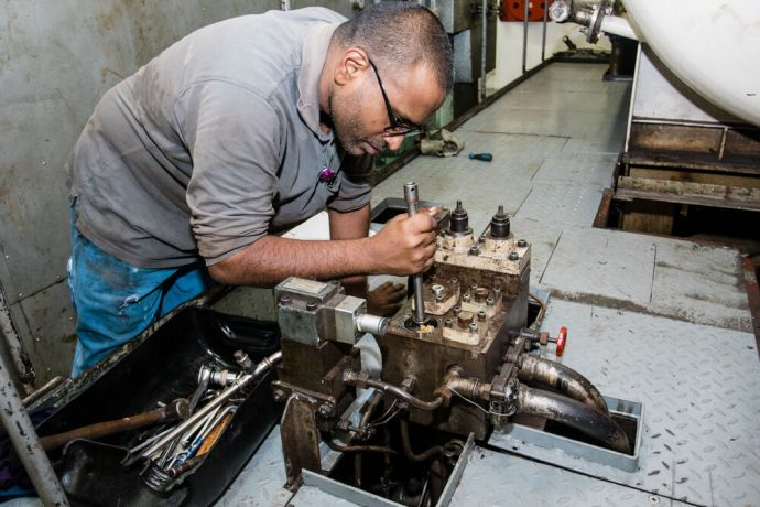 Jamaica: Kingston, Jamaica :: Herbert Devan (East Asia) working in the engine room. More Info