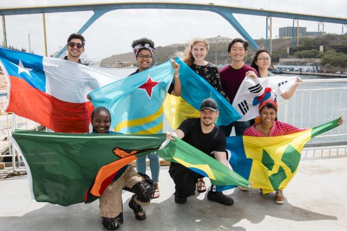 Curaçao: Caracas Bay, Curaçao :: Crewmembers from different nations display their flags on Logos Hopes outer deck. More Info