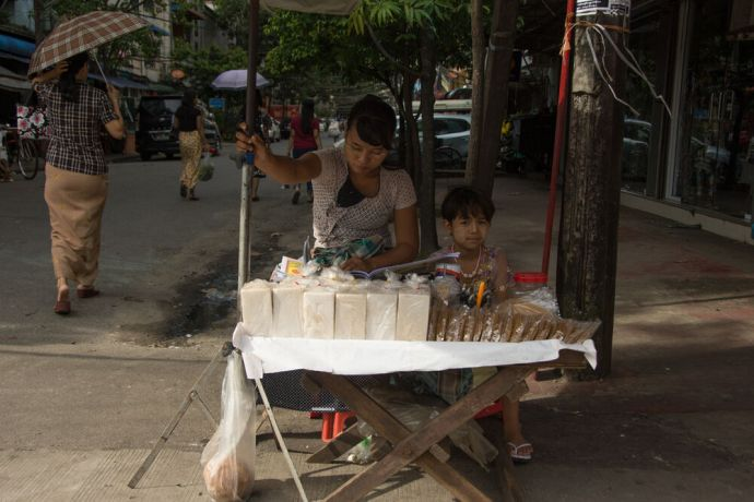 Myanmar: Mother and child selling goods on a sidewalk in Myanmar. Photo by Ellyn Schellenberg. More Info