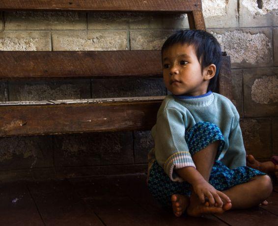 Myanmar: Boy in Myanmar sits on the floor in front of a bench. Photo by Ellyn Schellenberg. More Info