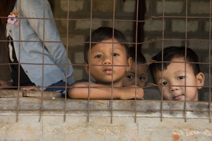 Myanmar: Children in Myanmar stare through an iron grid. Photo by Ellyn Schellenberg. More Info