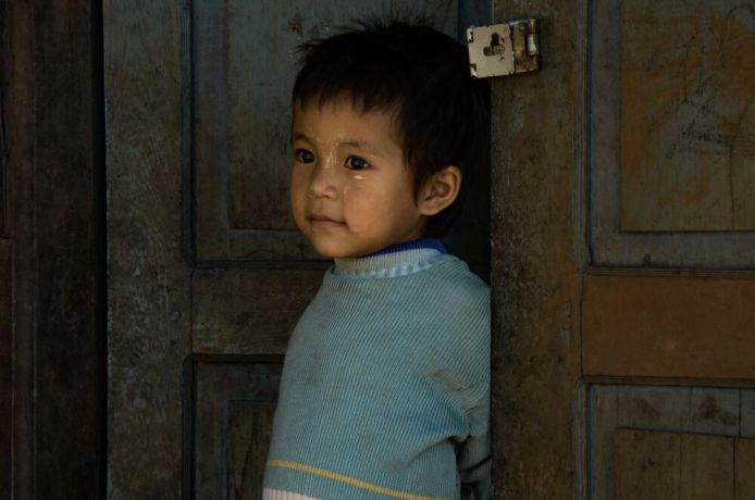 Myanmar: A boy stands at a door in Myanmar. Photo by Ellyn Schellenberg. More Info