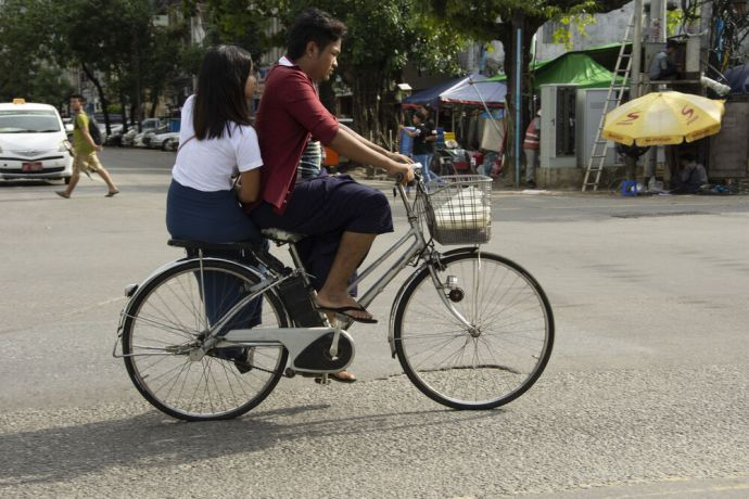 Myanmar: Couple ride on a bicycle in the streets of Myanmar. Photo by Ellyn Schellenberg. More Info