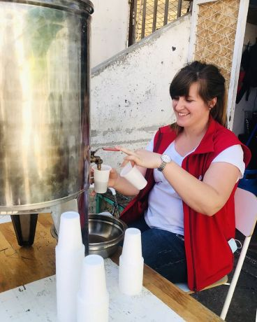 Serbia: Lidia pouring a drink at a refugee camp in Serbia. More Info