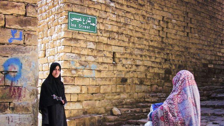 Arabian Peninsula: Two women in Yemen wearing traditional headdress stand at stairs on Isa (Jesus) Street. More Info