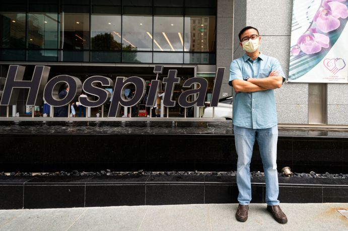 Singapore: Portrait of Staffer Alvin Tey standing outside a hospital. Photo by Alex Coleman. More Info