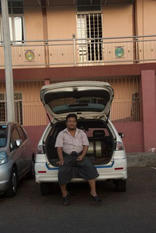 Myanmar: A taxi driver sits in the trunk of his car waiting for passengers in Myanmar near a Buddhist temple. More Info