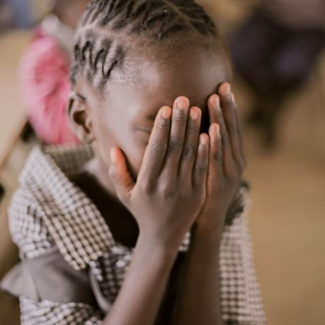 Zambia: Student covers face during prayer at Makwati School in Kabwe, Zambia. More Info