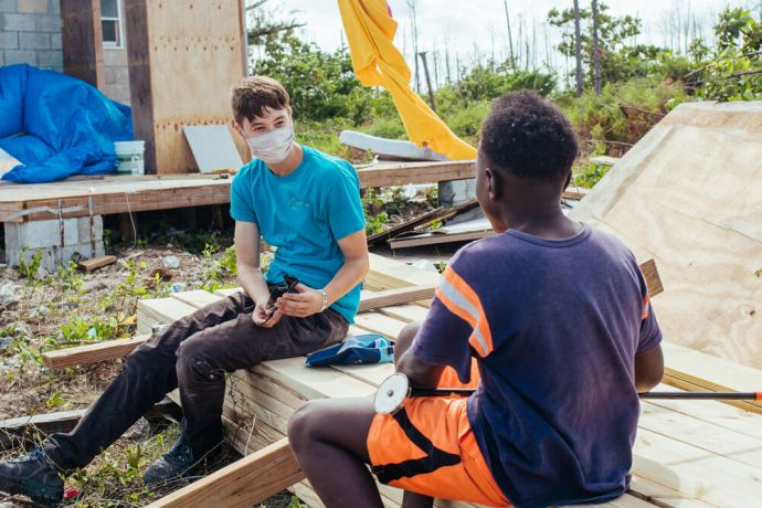 Bahamas: Abaco Islands, The Bahamas :: Marco Valerio (left, Argentina) talks to a boy while working on a house rebuilding project. More Info
